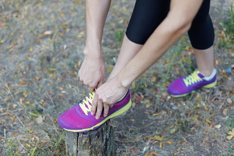 Female legs. Woman in black sportswear ties bright lilac sneakers with lime shoelaces, preparing for a jog, run or other fitness. stock image