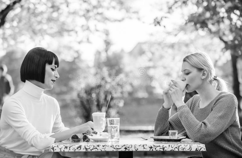 Female leisure. Girls friends drink coffee talk. Conversation women cafe terrace. Friendship friendly relations royalty free stock images