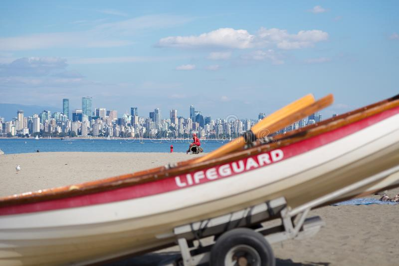 A female lifeguard watches over swimmers at Locarno beach, Vancouver. face blurred out stock image