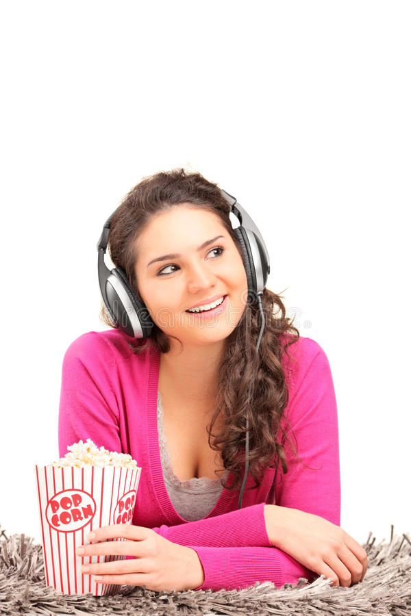 Female listening to music and eating popcorn stock photo