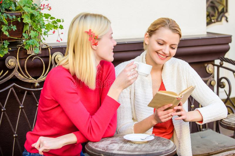 Female literature. Book every girl should read. Girls friends sitting cafe terrace drinking coffee. Reading inspiring. Book. Self improvement and education royalty free stock photos