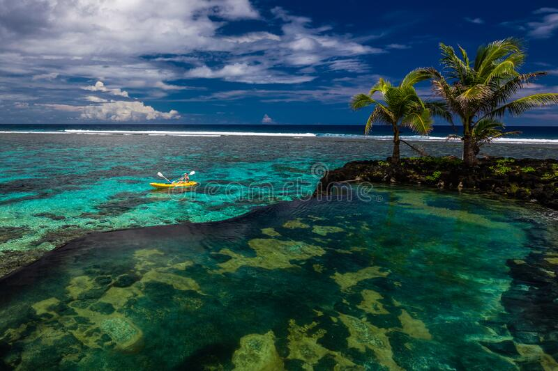 Female and little boy paddling canoe on a lagoon with coral reef stock images