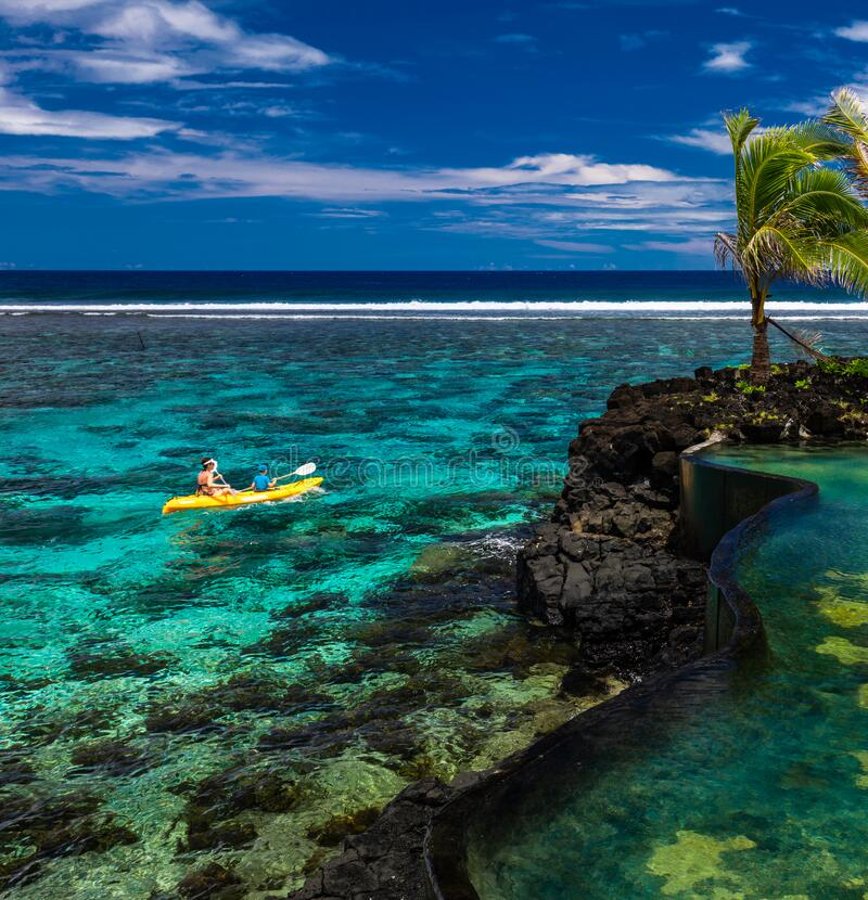 Female and little boy paddling canoe on a lagoon with coral reef royalty free stock photo