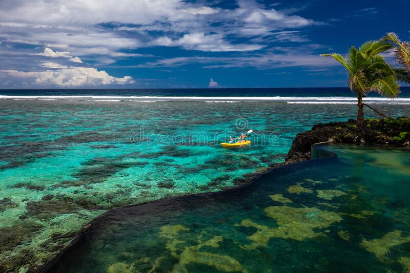 Female and little boy paddling canoe on a lagoon with coral reef royalty free stock image