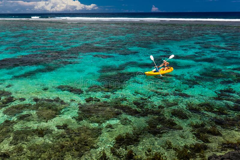 Female and little boy paddling canoe on a lagoon with coral reef royalty free stock photography