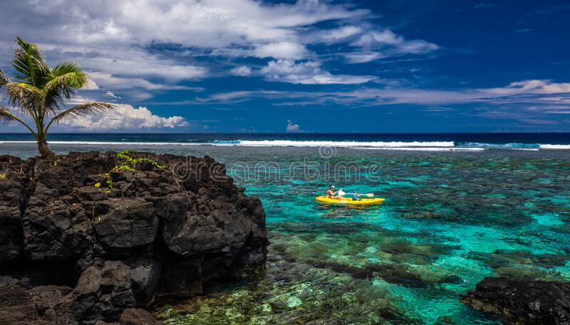 Female and little boy paddling canoe on a lagoon with coral reef stock photo