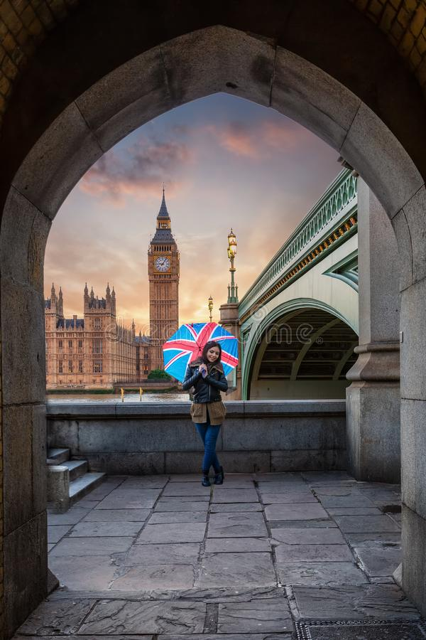 Female London tourist with a union jack umbrella in front of the Big Ben. Attractive female London tourist with a union jack umbrella stands in front of the stock images