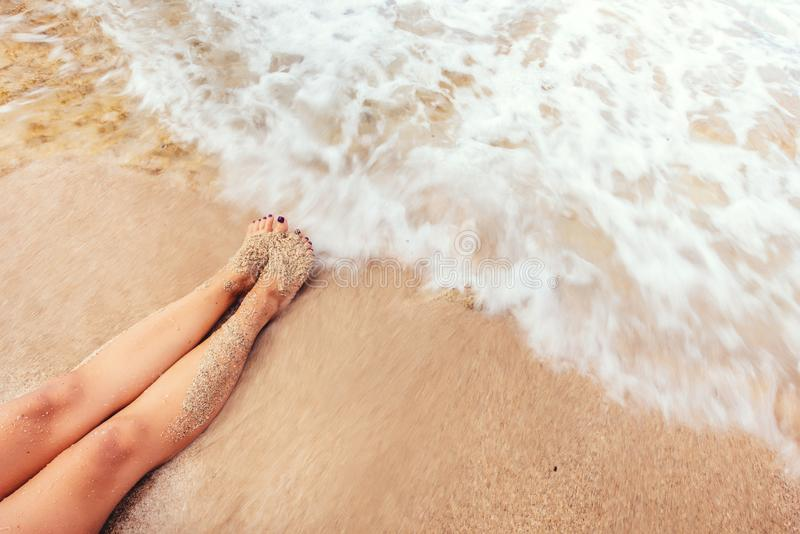 Female long feet meeting the sea wave. Summer vacations concept with sandy golden beach and foamy waves royalty free stock photos