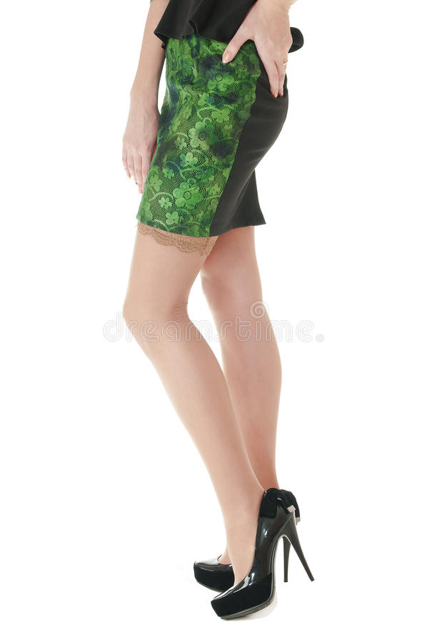 Female long legs shod in black shoes with high heels. Side view of female long legs in nylon beige stockings and shod in black shoes with high heels on white stock photography