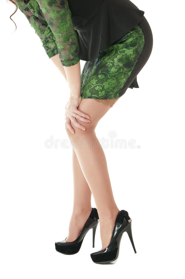 Female long legs shod in black shoes with high heels. Side view of female long legs in nylon beige stockings and shod in black shoes with high heels on white royalty free stock photography