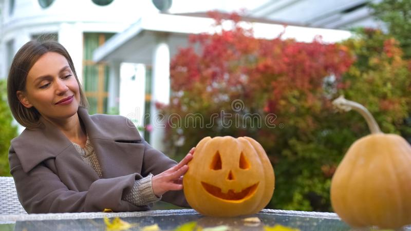 Female looking at pumpkin Jack lying on table, preparing for Halloween party. Stock photo royalty free stock image