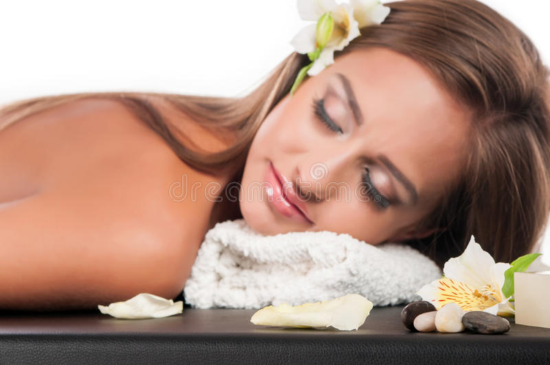Female during luxurious procedure of massage. Beautiful young woman having a massage in a spa royalty free stock photos