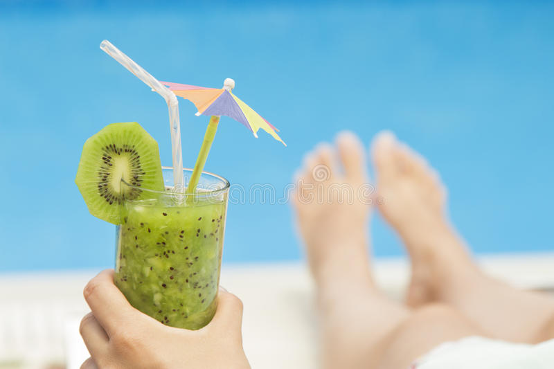 Female lying on sunbed and holding a glass of fresh kiwi smoothie royalty free stock images