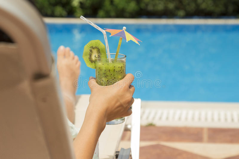 Female lying on sunbed and holding a glass of kiwi smoothie stock photos