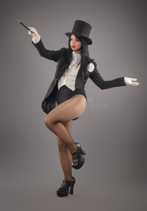 Female magician in costume suit with magic stick doing trick stock photos