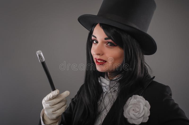 Female magician in costume suit with magic stick doing trick stock image