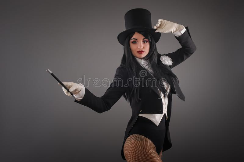 Female magician in costume suit with magic stick doing trick royalty free stock photography