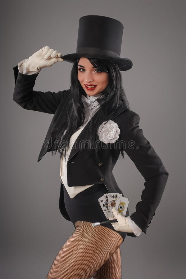 Female magician in performer suit with magic wand and playing ca royalty free stock images