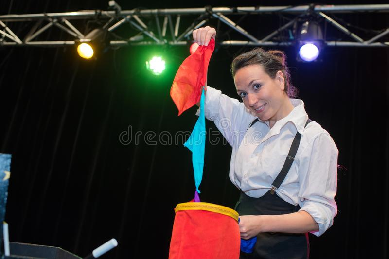 Female magician pulling length material from bag royalty free stock photo