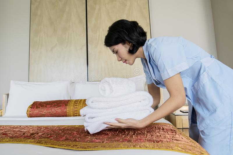 Female maid putting clean on the bed sheet stock images