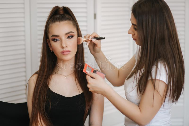 Female makeup master use a powder brush. Beautiful model in beauty studio. Professional make up artist finish fashion stock photos
