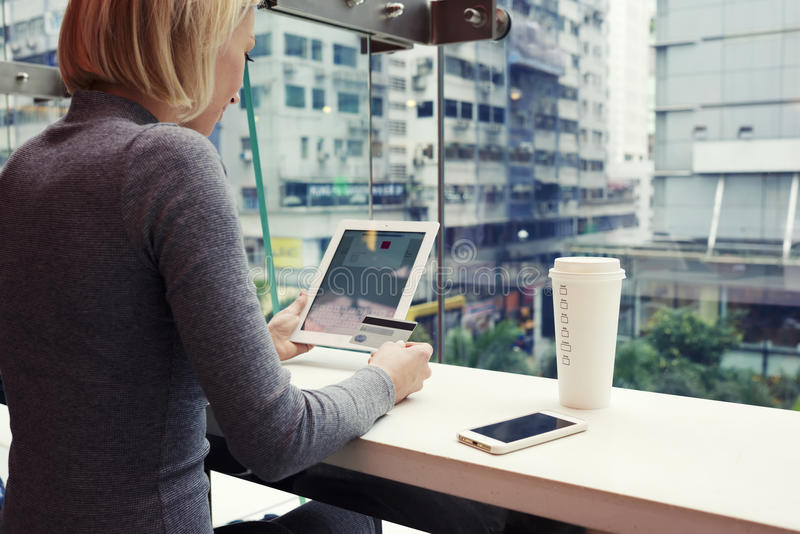Female is making shopping in internet via digital tablet, while is sitting in cafe royalty free stock images