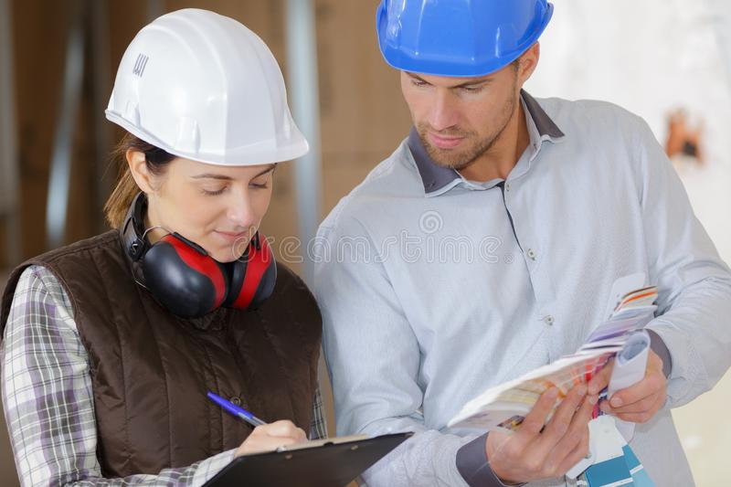 Female and male construction worker discussing over clipboard royalty free stock image