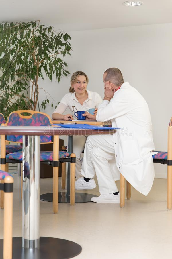 Female and male doctor in the breakroom of an hospital. Having a conversation or flirting stock photo