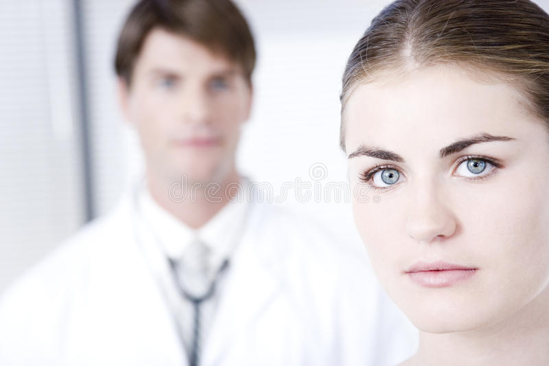 Female with male doctor out of focus in backgroundnn stock photos
