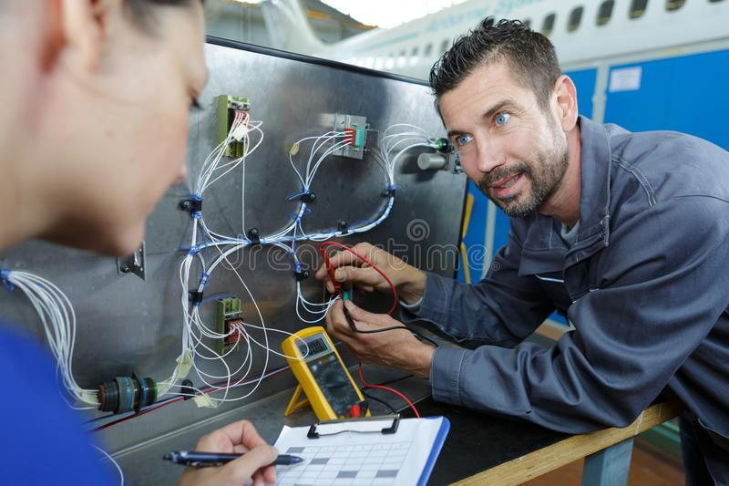 Female and male electrician measuring voltage in distribution board royalty free stock images