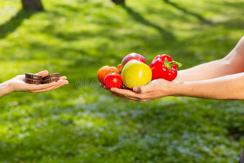 Female and male hands, holding and comparing cookie vs vegetables and fruits. Background of the green park stock photos