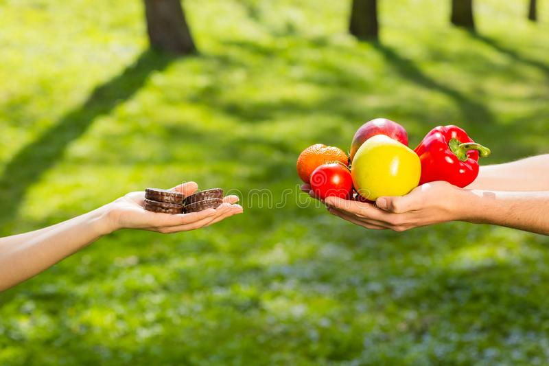 Female and male hands, holding and comparing cookie vs vegetables and fruits. Background of the green park stock image