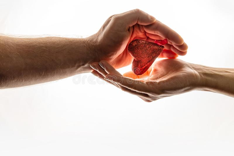 Female and male hands are keeping red heart together. Heart is between hands. World Compassion Day. stock photography