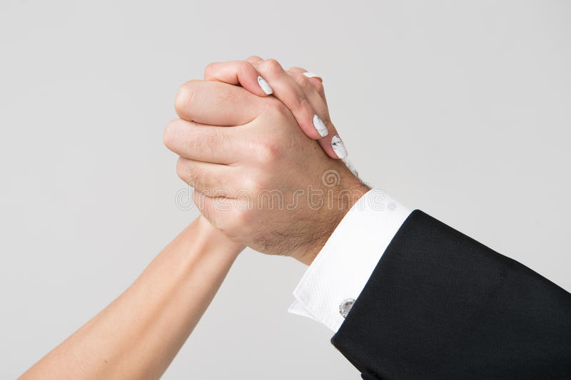 Female and male hands together touch and holds each other. Female and male hands of man and woman touch and hold each other as family in love gesture on grey stock photo