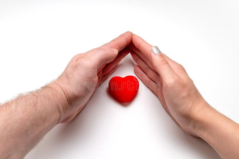 Female and male hands and red heart are on the white background/table. International Human Solidarity Day royalty free stock images