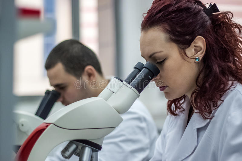 Female and male medical or scientific researchers or women and m. En doctors looking through a microscope in a laboratory. Young scientist doing some research stock image