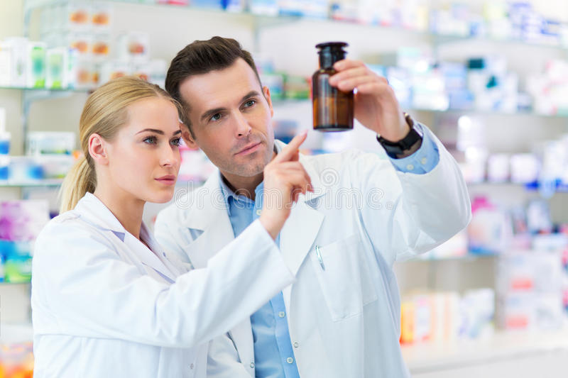 Female and male pharmacists. In pharmacy stock photography