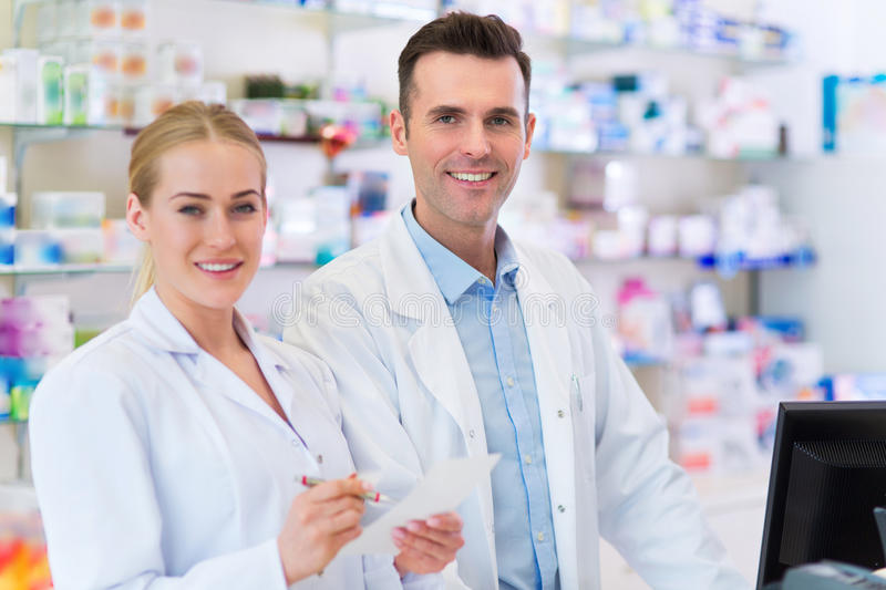 Female and male pharmacists. In pharmacy stock image