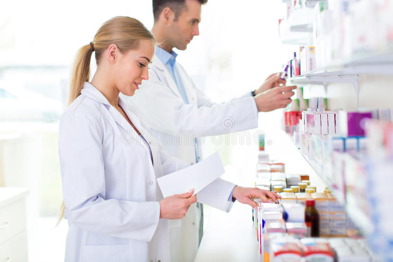 Female and male pharmacists. In pharmacy royalty free stock images