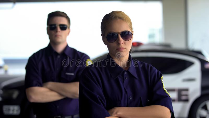 Female and male police officers with crossed hands looking into camera, security. Stock photo stock photography