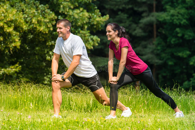 Female and male runner stretching outdoors royalty free stock image