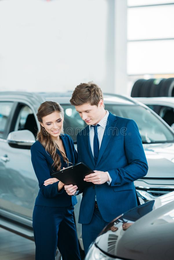 Female and male Sales managers of a car showroom standing and looking stock image