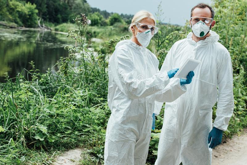 female and male scientists in protective masks and suits working with digital tablet and looking royalty free stock photo