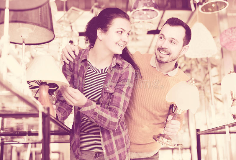 Female and male in shop of home appliances are choosing night la royalty free stock photography