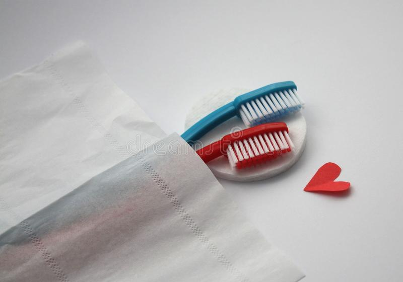 Female and male toothbrushes hugging in bed, visual metaphore of love royalty free stock photography