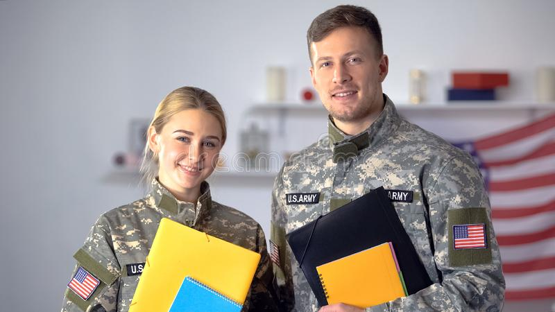 Female and male US military students with folders smiling at camera, education. Stock photo royalty free stock photo
