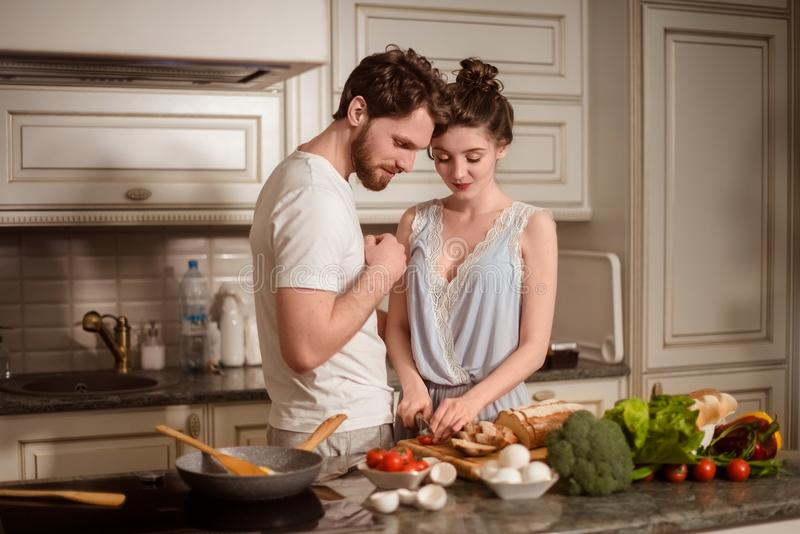 Female and male vegeterians stand together against kitchen interior, prepare vegetable salad. Family couple cook on cozy royalty free stock photo