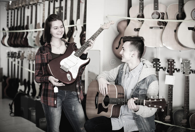 Female and male 14-21 years old are choosing between acoustic an royalty free stock image