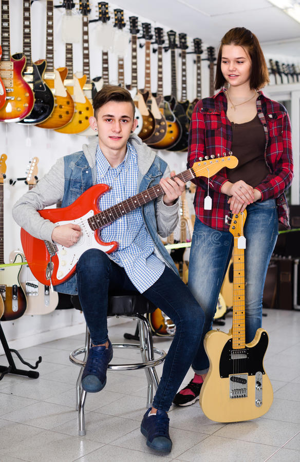 Female and male 15-19years old are deciding on suitable amp stock image