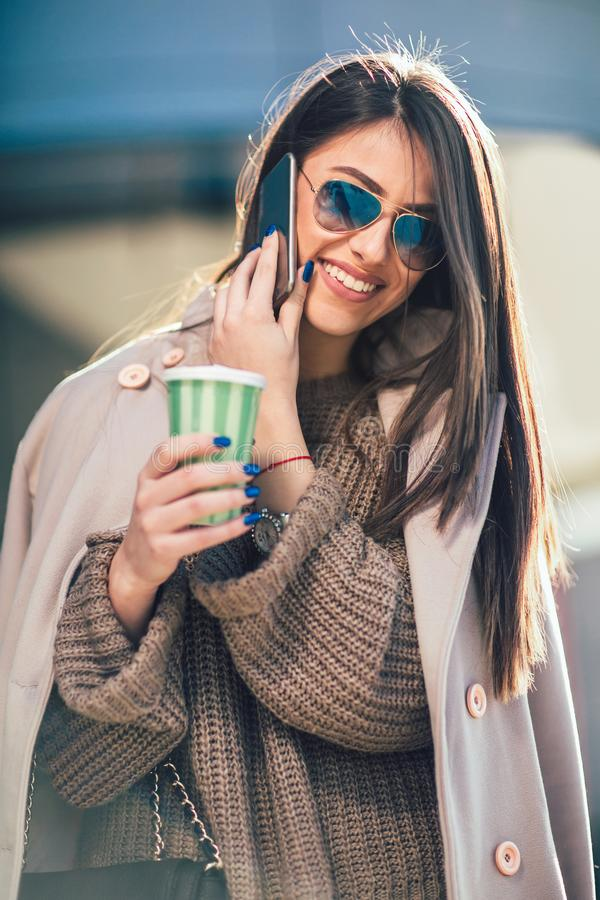 Female manage walking on city street and talking on mobile phone holding coffee to go royalty free stock photo